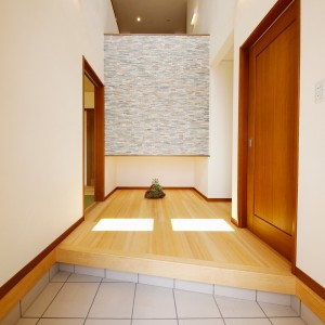 正面に天然石タイルを貼った玄関は、階段ホール部分を利用した吹き抜けに。右手扉の奥に大容量のクローゼットスペースを設けることで、靴箱は置かずスッキリした空間に。