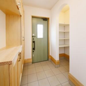 リーフグリーンの扉と無垢材の靴箱でナチュラルな雰囲気の玄関。1帖分の土間スペースには、可動棚を設けて使い易く、収納量もたっぷりです。