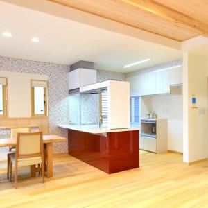 存在感のあるインテリアゲートのフラットキッチン。アッパーには調理中にボウルなどを仮置きできる昇降棚が、サイド部分にはまな板収納が付いています。