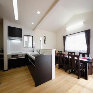 8人掛けテーブルを置ける広さを確保したダイニングルームと、そのすぐ近くに設置したL型のキッチン。コンロ横に食器棚やパントリーが続き、2方向から出入りできるようになっています。