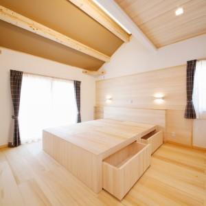 南側を勾配天井にした寝室。壁や天井の一部にももみの木を貼り、抽斗付きで4つに分割できるもみの木のベッドも造作しました。
