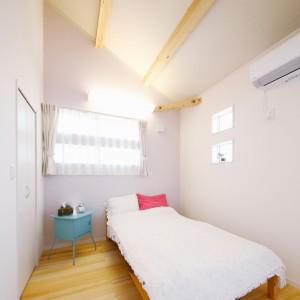 南東側の大通りから近いので、あえて大きな窓を設けず適度な籠り感のある寝室。淡いパープルの壁紙と水色のサイドテーブルで北欧風の可愛い空間に。