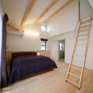 勾配天井の主寝室は奥に書斎スペースを設け、1面だけ腰壁を貼りました。手前の梯子階段を登ると塔屋~屋上バルコニーへと続きます。