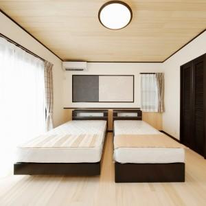 廻り縁や巾木、扉にダークブラウンを用いて空間にアクセントを付けた主寝室。壁の一部にエコカラットも貼りました。