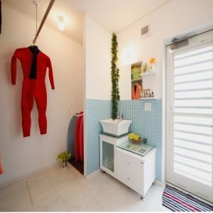 洗面脱衣室内に室内物干しとボード置場を確保しました。デザイン性の高い洗面台横の勝手口を出ると、すぐ脇に外シャワーも設置されたサーファー仕様です。