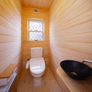 天井と壁全面にもみの木を貼ったトイレ。嫌な臭いを吸着・分解してくれるのでおすすめです。陶器の手洗い鉢もお洒落です。