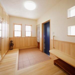 上り框をL字型にした玄関。シュークローゼットも床上に配置しているので上部にも手が届きやすくなっています。手摺とベンチも付けて昇降もスムーズ。ブルーの玄関扉がアクセントになっています。