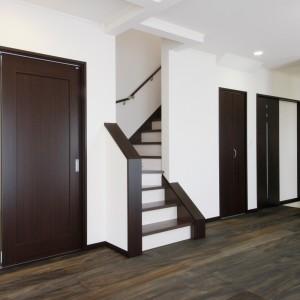 建具や床の色も含めホワイトとダークブラウンでコーディネートし、シックでモダンな印象の階段。2階間取りの都合上、リビング側に2段突き出していますが、コーナー収納棚やフロア照明、観葉植物などを飾ると納まりも良くなります。