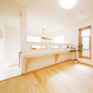 吹き抜けで開放感ある階段ホールは室内物干しスペースも兼ねて広めに確保。長いカウンターテーブルは使い道いろいろです。勝手口の奥はベランダになっています。