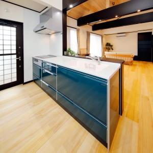 ブルーグリーンの扉面が目に鮮やかな対面キッチン。対面にTVを置くようになっているので、TVを見ながら、家族の様子も見つつ料理ができます