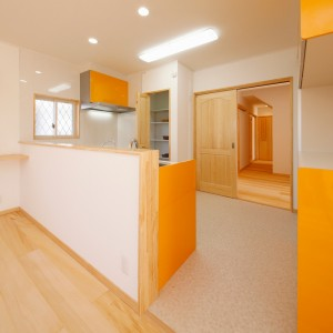 明るいオレンジ色のL型キッチンとキャビネット、奥にパントリーを組み合わせた変形型。パントリーは土間になっていて勝手口も付いているので、ゴミ出しもスムーズ。