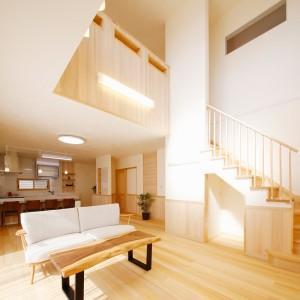 格子手摺のリビング階段と大きな吹き抜けで開放感のあるリビングダイニング。階段下も収納スペースとして利用できるようにしています。