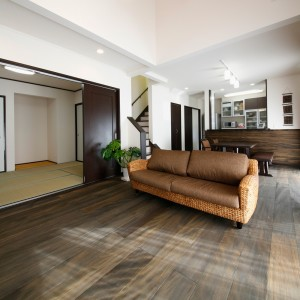 自然素材の塗料でダークブラウンに塗ったもみの木の床のリビング。ウォーターヒヤシンスで編まれたソファーや観葉植物を置いて、アジアンリゾートな雰囲気に。