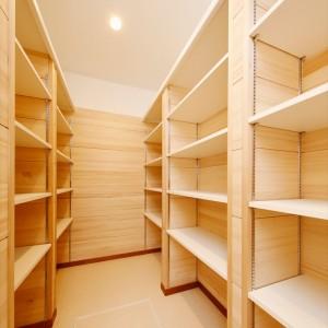 両面に可動棚を設置した、大容量のパントリー兼納戸。調湿、防カビ、防臭効果を期待して、枕棚より下の壁にはもみの木を貼りました。