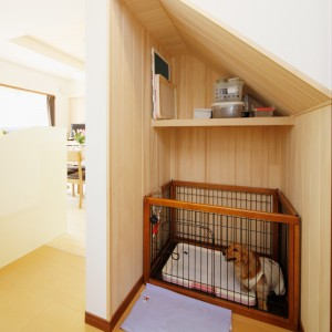 階段下を利用して設えたワンちゃんスペース。隙間に埃が溜まりにくいよう、ケージの大きさに合わせてピッタリにサイズ調整。壁面にもみの木を貼って消臭対策をしています。