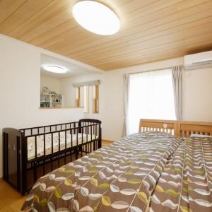 天井全面にもみの木を貼った主寝室。奥に設置した書斎コーナーは、背面に大きな書棚も造り付けてあるので、コンパクトながら機能的です。